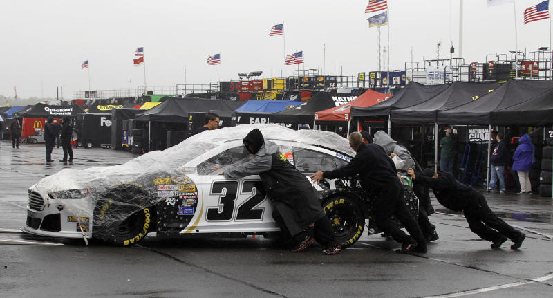 Crew members push the car of Timmy Hill through the garage area during inspections for Sunday's NASCAR Sprint Cup Series Pocono 400 auto race, Friday, June 7, 2013, in Long Pond, Pa. (AP Photo/Russ Hamilton Sr.)