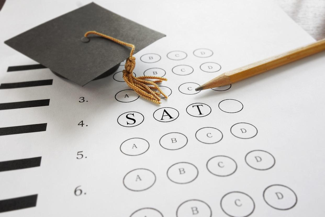 SAT test with pencil and mortar board graduation cap