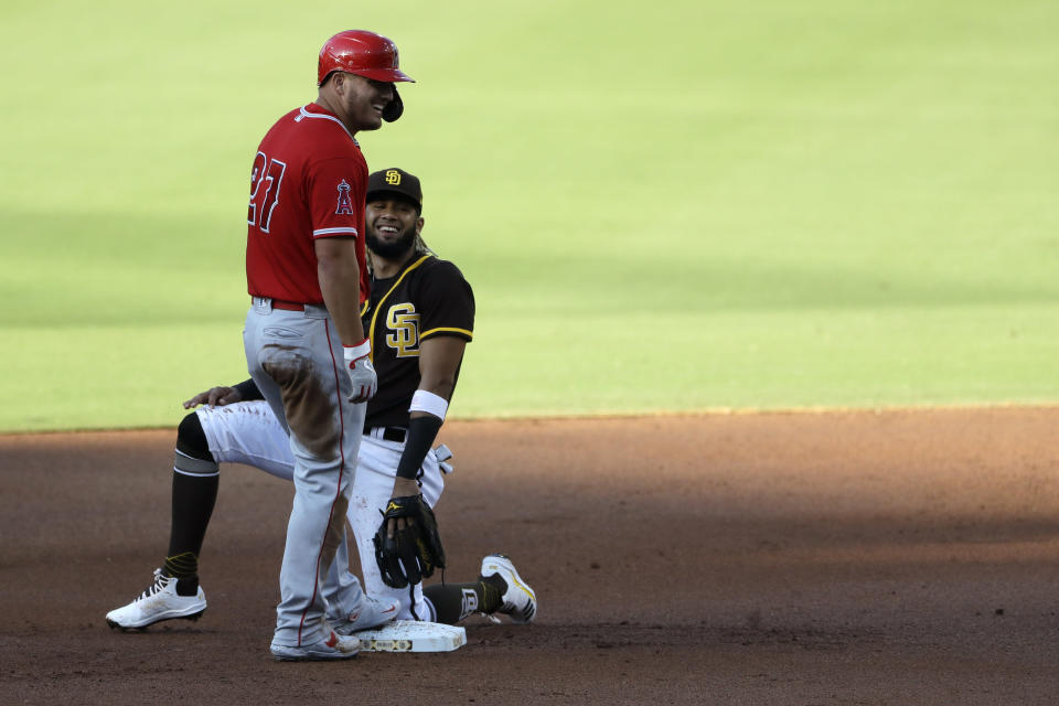 San Diego Padres shortstop Fernando Tatis Jr., right, jokes with Los Angeles Angels' Mike Trout after Trout arrived safely at second base off a throwing error by starting pitcher Garrett Richards during the first inning of an exhibition baseball game at Petco Park, Monday, July 20, 2020, in San Diego. (AP Photo/Gregory Bull)