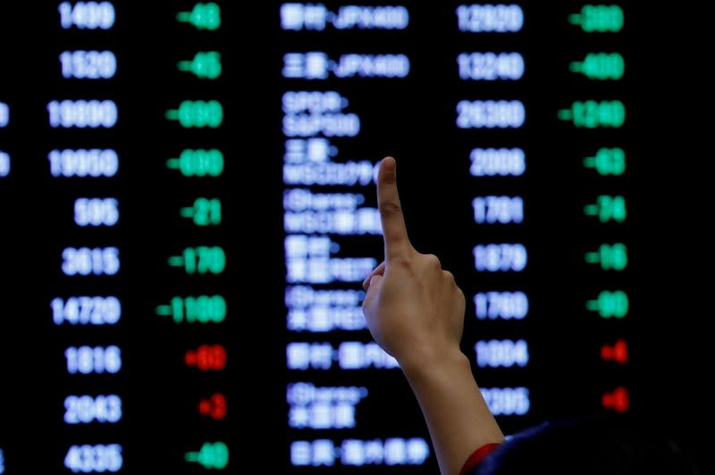 FILE PHOTO: A woman points to an electronic board showing stock prices as she poses in front of the board after the New Year opening ceremony at the Tokyo Stock Exchange (TSE)