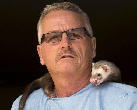 Pat Wright poses with Jethro, one of his three pet ferrets, at his home in La Mesa, California August 17, 2015.  REUTERS/Mike Blake