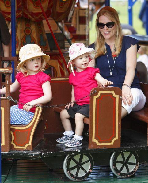 <p>Princess Anne's daughter-in-law, Autumn Phillips, takes daughters Savannah and Isla on a train-themed merry-go-round at the Royal Windsor Horse Show. </p>