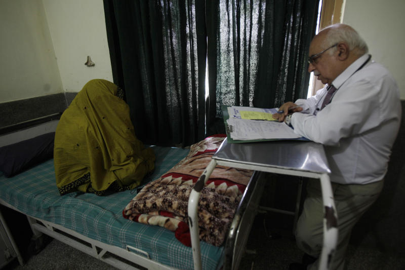 In a photo made on July 3, 2012, Pakistani psychiatrist Mian Iftikhar Hussain talks to a woman who suffers from severe depression after her cousin was killed by a mortar, at a local hospital in Peshawar, Pakistan. The plights of people who survived deadly bombings have become increasingly common in Pakistan's northwest, the main Taliban sanctuary in the country where psychiatrists estimate millions are suffering post-traumatic stress disorder and other psychological illnesses.(AP Photo/Mohammad Sajjad)