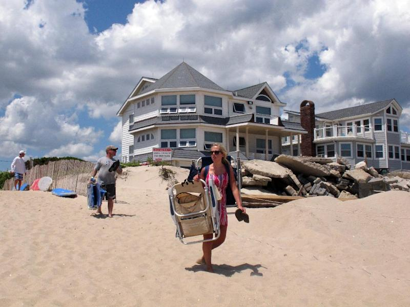 In this July 5, 2013 photo, beachgoers pass the rubble of storm-damaged houses as they walk onto the beach in Point Pleasant Beach, N.J. A wave of large property tax increases that had been feared in the aftermath of Superstorm Sandy has not materialized thanks to large amounts of federal aid, borrowing by towns, and the use of rainy-day surplus funds. (AP Photo/Wayne Parry)
