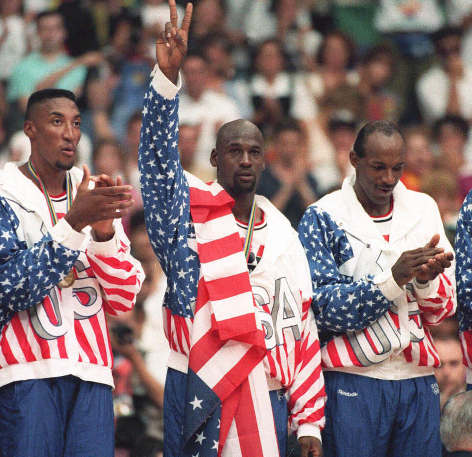 FILE - In this Aug. 8, 1992, file photo, the United States' Michael Jordan, center, poses with his gold medal and a flag draped over his shoulder at the Summer Olympics in Barcelona. (AP Photo/Susan Ragan, File)