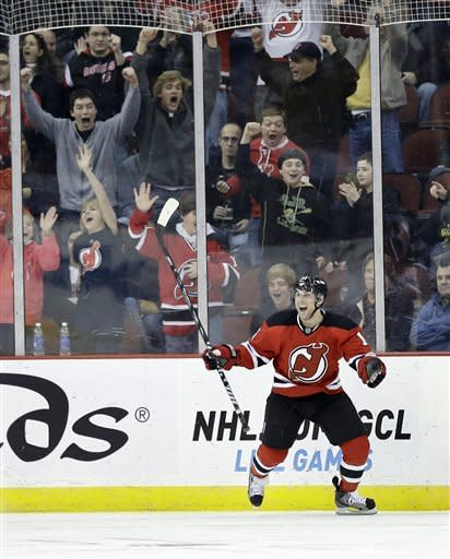 Fans celebrate with New Jersey Devils' Stephen Gionta (11) after his goal during the first period of an NHL hockey game against the Winnipeg Jets in Newark, N.J., Sunday, March 10, 2013. (AP Photo/Mel Evans)