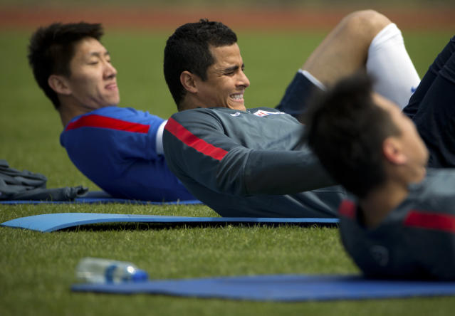 In this Thursday, April 9, 2015 photo, Colombian soccer player Giovanni Moreno, center, stretches with his Shanghai Shenhua teammates as they warm up during practice at the team's training facility in Shanghai. While a few years ago Chinese Super League (CSL) soccer was mired in corruption scandals and poor play, Shenhua is emblematic of the new and improved CSL - it's increasingly globalized, brimming with newfound professionalism and flush with cash. (AP Photo/Mark Schiefelbein)