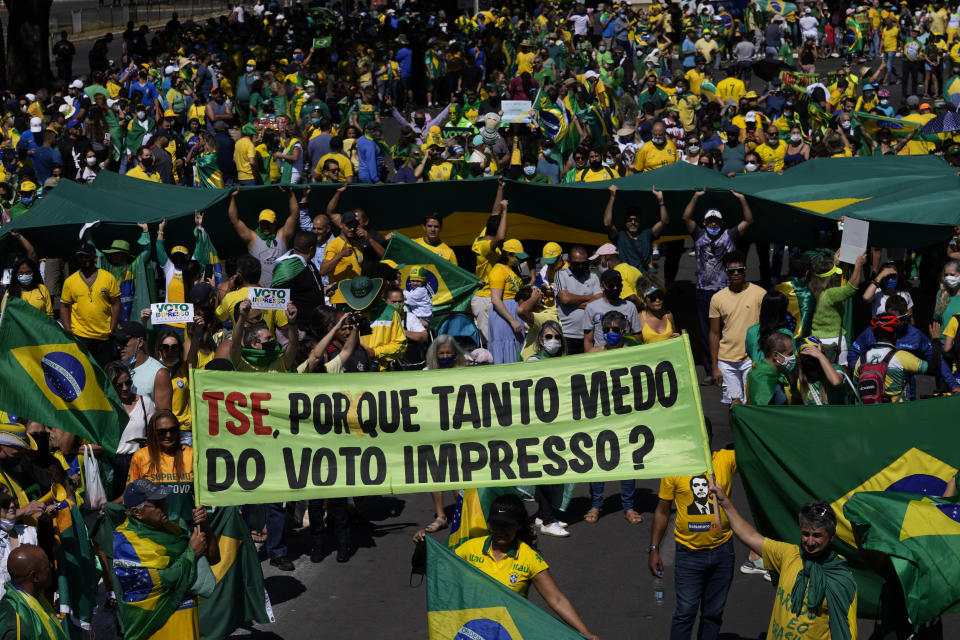 """Supporters of Brazil's President Jair Bolsonaro carry a banner that reads in Portuguese phrase """"TSE, why so afraid of the printed vote,"""" referring to the Supreme Electoral Tribunal, during a pro-Bolsonaro rally at the Esplanade of Ministries, in Brasilia, Brazil, Sunday, Aug. 1, 2021. Political backers of President Bolsonaro have called for nationwide rallies to express their support for the embattled leader and his call for adding printouts to the electronic voting system. (AP Photo/Eraldo Peres)"""