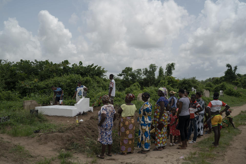 A man paints the grave stone of a relative in white, as a symbol that the soul of the deceased remains in peace, as members of the family stand by, during the Day of the Dead celebrations in Abidjan, Ivory Coast, Monday, Nov. 2, 2020. (AP Photo/Leo Correa)