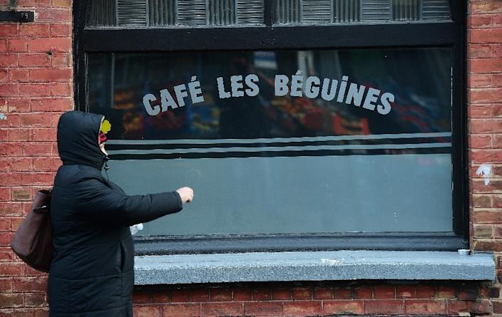 """A woman walks past the bar """"Les Beguines"""", owned by Brahim Abdeslam, one of the suicide bombers implicated in the Paris attacks, in Molenbeek on November 17, 2015 (AFP Photo/Emmanuel Dunand)"""