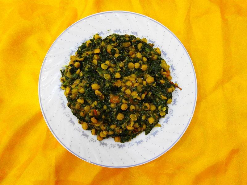 """<p>A delicious dry preperation of dal. Cook 1/2 cup Chana dal (bengal gram) with salt, turmeric powder & enough water in pressure cooker till done. Reserve. In a kadhai add 1 tsp oil, some mustard seeds, curry leaves & hing. Add one chopped green chili & one chopped onion. Cook till golden brown. Add 1/2 th cup chopped spinach & stir fry for few minutes. Add cooked chana dal, chili powder & adjust salt. Cook till water evaporates. Serve with hot rotis. """"Creative Commons Chanay Ki Daal Aur Palak"""" by Miansari66 is licensed under CC BY 1.0 </p>"""
