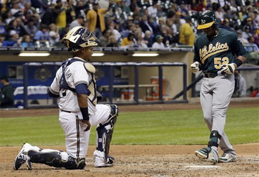 Milwaukee Brewers catcher Martin Maldonado watches as Oakland Athletics' Yoenis Cespedes crosses the plate after hitting a home run during the sixth inning of a baseball game Tuesday, June 4, 2013, in Milwaukee. (AP Photo/Morry Gash)