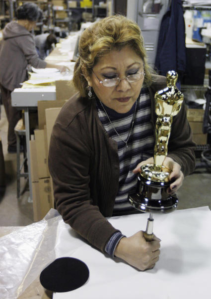 FILE - In this Jan. 26, 2009 file photo, Bertha Fuentes assembles the statue and the base of an Oscar statuette at R.S. Owens & Co., in Chicago. The company said it will be laying off 95 workers on Dec. 17, 2012. The cuts come a month after R,.S. Owens announced it was being purchased on Dec. 17 by St. Regis Crystal Inc. of Indianapolis. The company has about 250 employees. A news release on the sale said the company will continue to make Oscar and Emmy statues in Chicago. They have been making the Oscar statues for about 30 years. (AP Photo/M. Spencer Green, File)