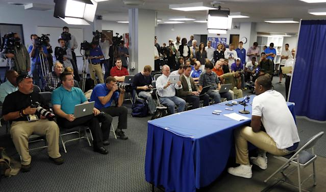 Kentucky's Julius Randle, bottom right, announces he will leave after one season to enter the NBA draft during a news conference in Lexington, Ky., Tuesday, April 22, 2014. (AP Photo/James Crisp)