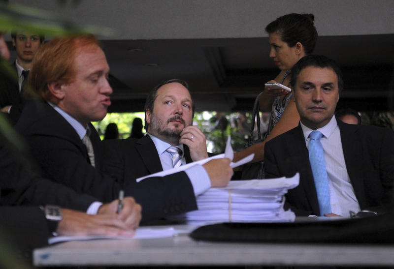 ** CORRECTS SPELLING OF SECOND REFERENCE TO SABBATELLA INSTEAD OF SABATELLA ** Martin Sabbatella, center, head of the government media regulation body, Federal Authority on Audiovisual Communication Services (AFSCA) and Sergio Surano, right, director of the AFSCA legal department, listen as Grupo Clarin's lawyer Damian Cassino, left, speaks during a meeting, in Buenos Aires, Argentina, Monday, Dec. 17, 2012. Sabbatella said Monday that the government will make the conglomerate and other companies comply with the law, which bars any company from owning too many different media properties. The law could require Grupo Clarin to sell off broadcast licenses as well as its majority stake in Cablevision, the cable TV network that has become the company's cash cow. (AP Photo/Daniel Dabove,Telam)