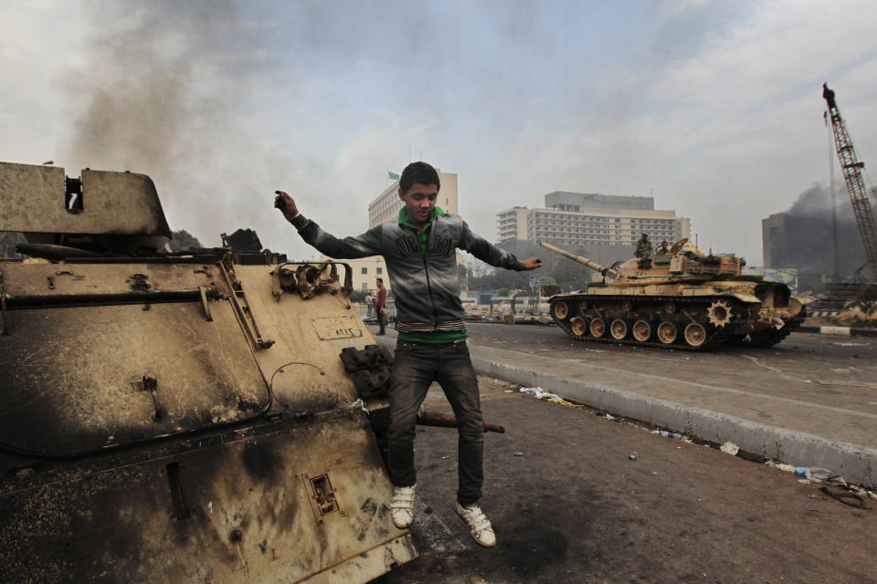 FILE - In this Jan. 29, 2011 file photo, a protester jumps from a burned armored personnel carrier in Tahrir Square, Cairo, Egypt. The 2011 uprising led to the quick ouster of autocrat Hosni Mubarak. A decade later, thousands are estimated to have fled abroad to escape a state, headed by President Abdel Fattah el-Sissi, that is even more oppressive. (AP Photo/Lefteris Pitarakis, File)