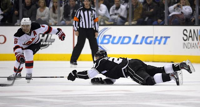 Los Angeles Kings right wing Matt Frattin, right, dives for the puck as New Jersey Devils defenseman Andy Greene pokes it away during the first period of an NHL hockey game on Thursday, Nov. 21, 2013, in Los Angeles. (AP Photo/Mark J. Terrill)