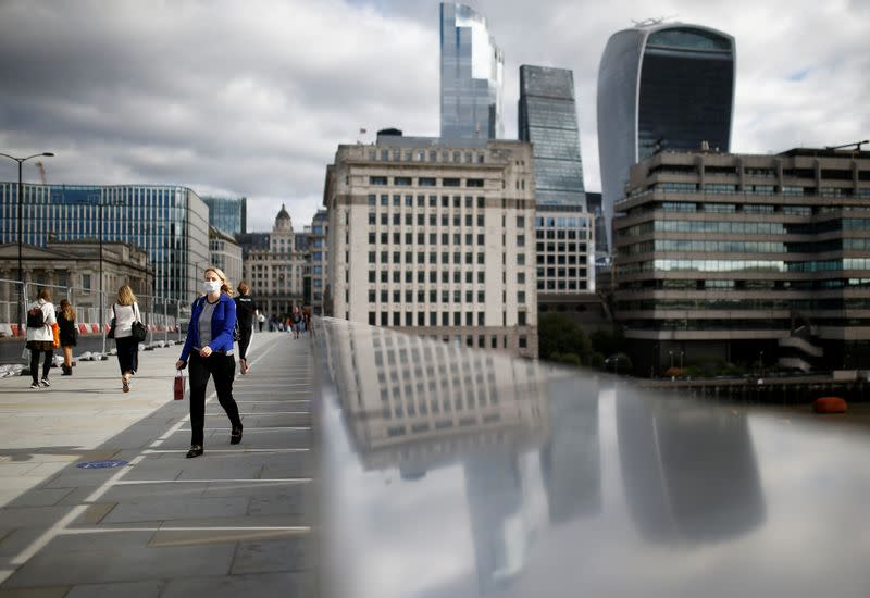 The financial district can be seen as a woman wearing a protective face mask walks over London Bridge, amid the coronavirus disease (COVID-19) outbreak, in London