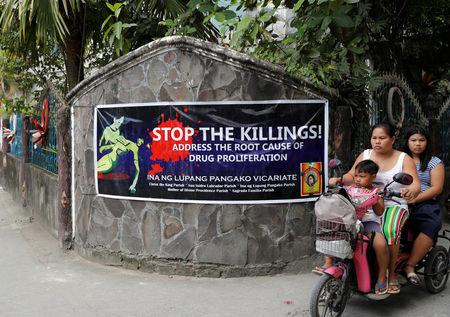 Residents ride a motorcycle past a banner opposing drug related killings along a street in Barangay Bagong Silangan,  Quezon City, Metro Manila, in the Philippines November 22, 2017.    REUTERS/Erik De Castro