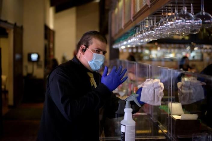 An employee at the Picos restaurant in Houston wears gloves and a mask as the restaurant reopened with 25 percent capacity on May 1 (AFP Photo/Mark Felix)