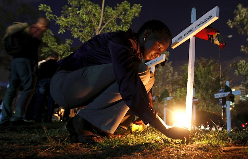 "A woman lights a candle on a wooden cross after a memorial concert for the Garissa university students who were killed during an attack by gunmen, at the ""Freedom Corner"" in Kenya's capital Nairobi April 14, 2015. Kenya gave the United Nations three months to remove Dadaab camp, housing 350,000 registered Somali refugees, as part of its response to the killing of 148 people in nearby Garissa by a Somali Islamist group. REUTERS/Thomas Mukoya      TPX IMAGES OF THE DAY"
