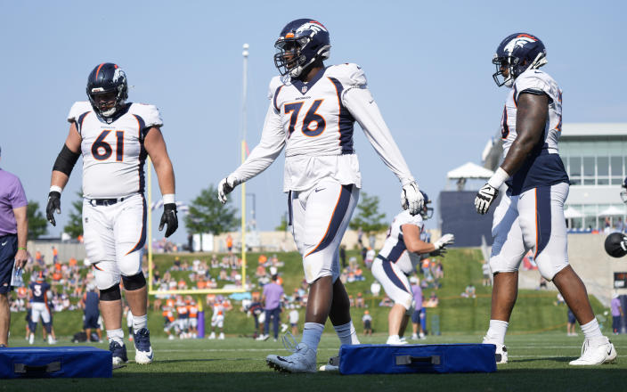From left, Denver Broncos offensive guard Graham Glasgow, offensive tackle Calvin Anderson and offensive tackle Bobby Massie take part in drills during an NFL football training camp at the team's headquarters Wednesday, Aug. 18, 2021, in Englewood, Colo. (AP Photo/David Zalubowski)