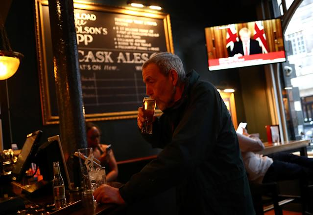 A man with a drink at a pub in London as Boris Johnson, pictured on the television screen, orders the closure of UK pubs. (REUTERS/Hannah McKay)