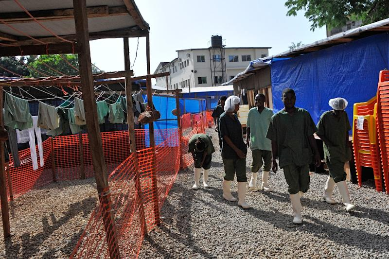 Workers walk at the Donka Ebola treatment center on May 2, 2015 in Conakry