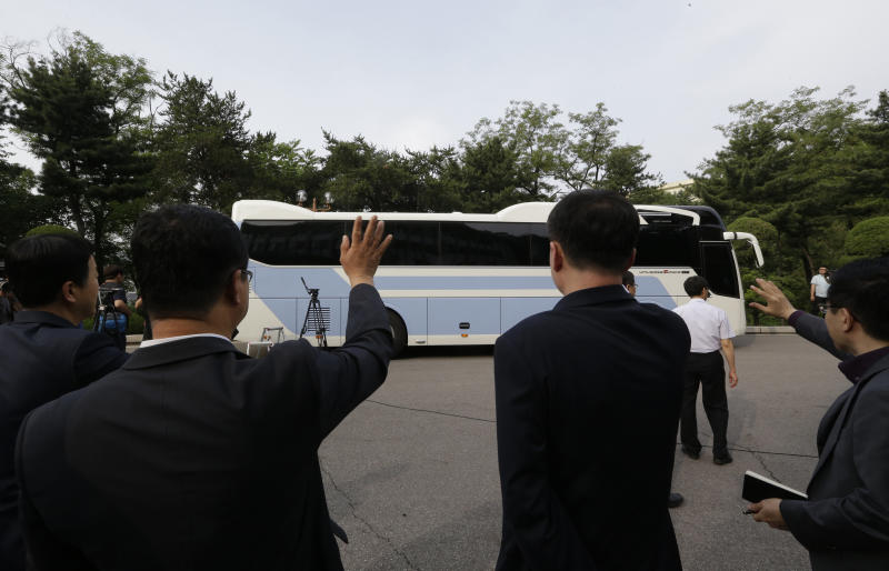 South Korea's Vice Unification Minister Kim Nam-sik, second from right, waves with other officers to a bus carrying a South Korean delegation as it leaves for Panmunjom at the Office of the South Korea-North Korea Dialogue in Seoul, South Korea, Sunday, June 9, 2013. North and South Korea will meet in the village straddling their heavily armed border Sunday for the first government-level talks on the peninsula in more than two years as they try to lower tension and restore stalled projects that once symbolized their rapprochement. (AP Photo/Lee Jin-man)