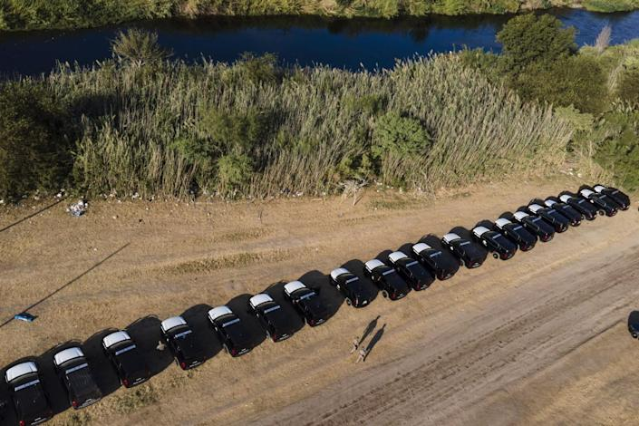 A line of Texas Department of Safety vehicles lines the bank of the Rio Grande.