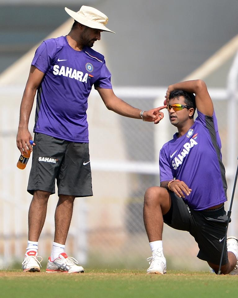 Indian cricketer Harbhajan Singh (L) jokes with teammate Pragyan Ojha during a training session on the third day of a three day camp at the Cricket Club of India (CCI) in Mumbai on November 11, 2012. The Indian cricket team has opted for a three day training camp ahead of their upcoming four test series against England.    AFP PHOTO/ INDRANIL MUKHERJEE