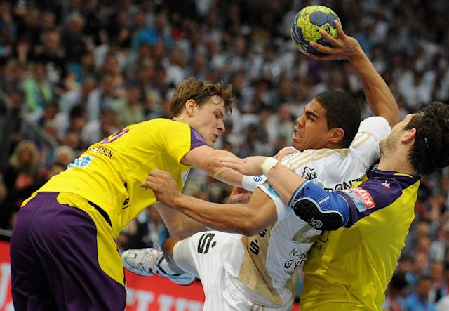 Kiel's Daniel Narcisse (C) vies with two players of Berlin during the Handball Champions League EHF Final Four semi final match Fuechse Berlin vs THW Kiel on May 26, 2012 in Koeln, western Germany. Kiel won the match 25-24. AFP PHOTO JONAS GUETTLER GERMANY OUTJONAS GUETTLER/AFP/GettyImages