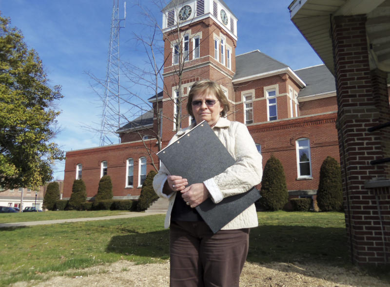 "In this Thursday, April 4, 2013 provided by Len Wells at WFIW News in Fairfield, Ill., Wayne County Clerk Glenda Young stands outside the Wayne County Courthouse in Fairfield with a book of property records. Many southern Illinois counties have scored a bonanza from a land rush linked to the debated drilling practice speculators believe can tap long-inaccessible oil and natural gas. Hundreds of thousands of dollars of fees have flowed into county coffers by hordes of ""land men,"" often out-of-staters who converged in recent years to scour title records for prime drillable parcels. Young estimates her office has collected $200,000 in such fees since 2011, plowing a chunk of that money into a soon-to-be-completed push to put her records online. (AP Photo/WFIW News, Len Wells)"