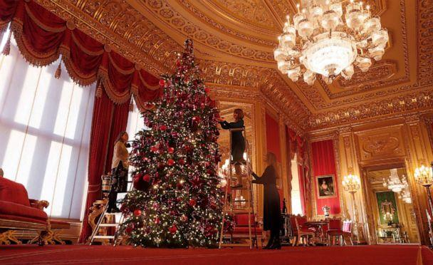 PHOTO: Staff adjust decorations on a Christmas tree in the Crimson Drawing room at Windsor castle during a media preview in Windsor, England, Nov. 29, 2019. (Alastair Grant/AP)