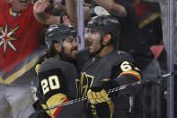 Vegas Golden Knights center Chandler Stephenson (20) cheers on left wing Max Pacioretty (67), who scored a goal against the Minnesota Wild during the second period of Game 7 of an NHL hockey Stanley Cup first-round playoff series Friday, May 28, 2021, in Las Vegas. (AP Photo/Joe Buglewicz)