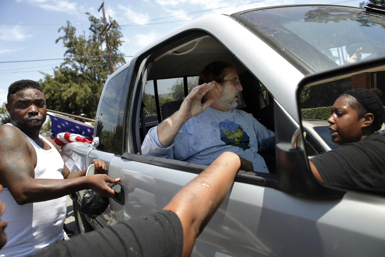 """Counter-protesters try to open the door of a pickup truck occupied by two men who drove near the Los Angeles office of U.S. Rep. Maxine Waters in Los Angeles on Thursday, July 19, 2018. Counter-protesters gathered at the field office of Waters, a black Democrat critical of President Donald Trump, to respond to a planned rally by members of a self-styled militia group who didn't appear to protest at Waters' office. Counter-protesters later took the U.S. flag from the back of this truck and burned it. Someone yelled, """"This is not the American flag, this is their flag."""" (AP Photo/Jae C. Hong)"""