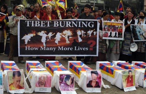 Tibetans offer prayers near mock coffins for the victims self-immolation during a rally in Siliguri on February 8