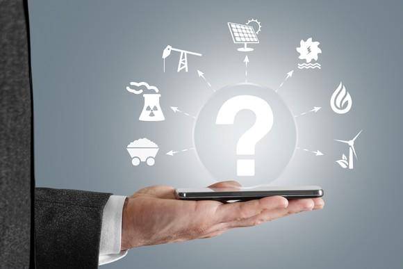 A businessman holding out his smartphone with various icons of energy sources floating above it with a question mark.