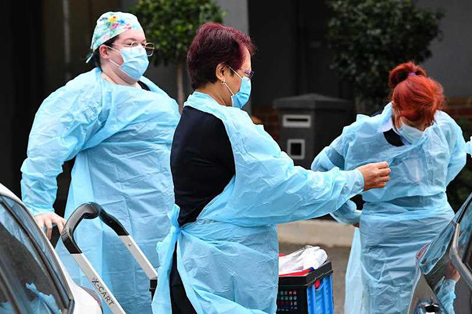 Healthcare workers don personal protective equipment before entering the Arcare Aged Care facility in Maidstone, Melbourne.