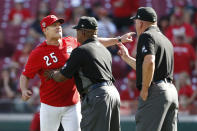 Cincinnati Reds manager David Bell (25) is restrained by umpire Laz Diaz, center, after being ejected by Jeff Nelson, right, following an argument over Reds' Eugenio Suarez being hit by a pitch by Pirates' Clay Holmes during the eighth inning of a baseball game against the Pittsburgh Pirates, Wednesday, May 29, 2019, in Cincinnati. The Pirates won 7-2. (AP Photo/Gary Landers)