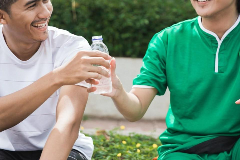 friend giving water bottle after exercising outdoor together