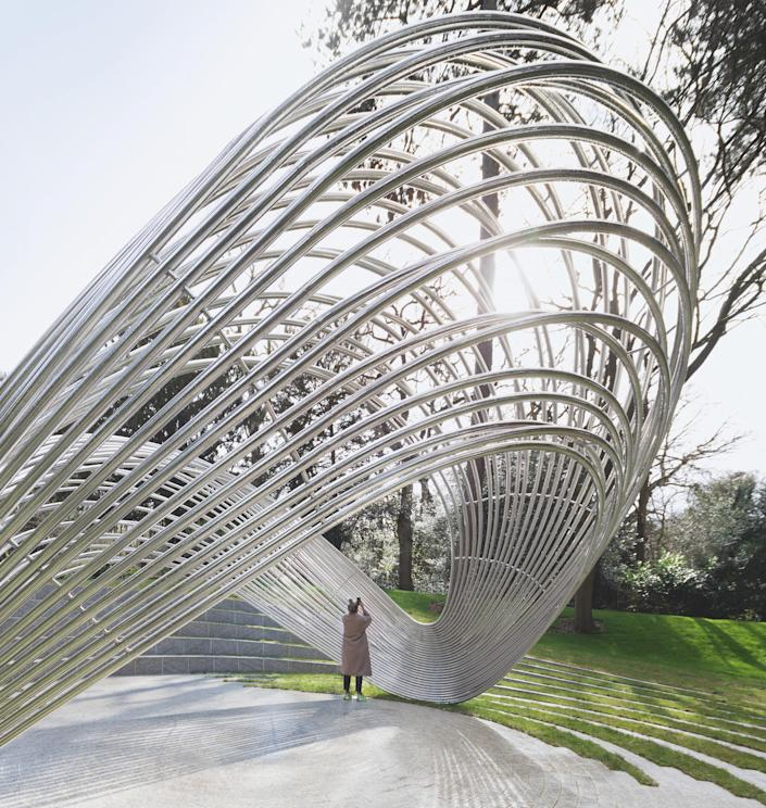 """Titled <em>Infinite Wave,</em> architect George King's 2019 memorial to the 31 British nationals killed in terrorist attacks in Tunisia in 2015 was inspired by flowing water. The structure is made up of 31 steel tubes that create a """"wavelike arch"""" and is surrounded by concentric circles of granite. The shape of the memorial changes based on the vantage point, resembling a set of wings from the side and an eye from above."""