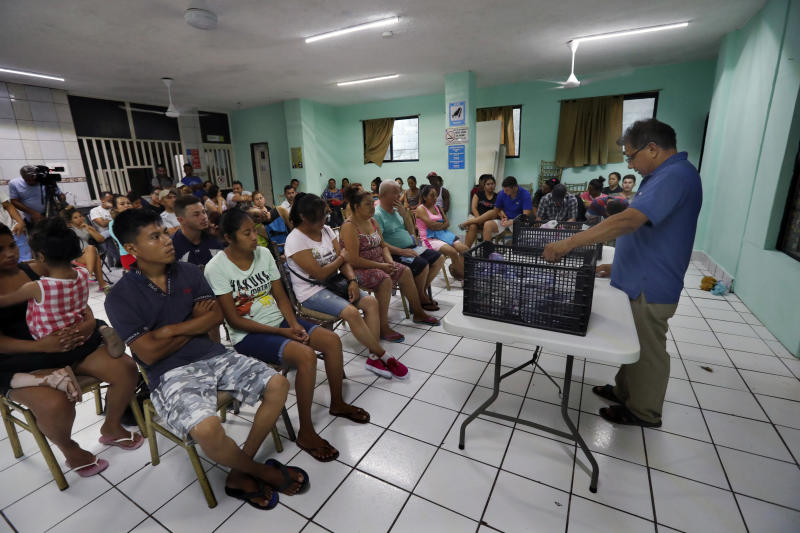 In this July 17, 2019 photo, Rev. Aaron Mendez talks with migrants at the AMAR migrant shelter, in Nuevo Laredo, Mexico. Officials in the Mexican border state of Tamaulipas say the pastor was abducted Aug. 3 from the shelter he ran in the dangerous border city of Nuevo Laredo. (AP Photo/Marco Ugarte)