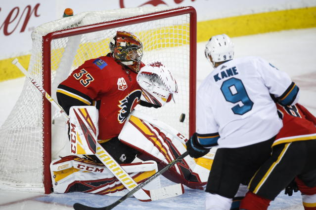 San Jose Sharks' Evander Kane, right, scores on Calgary Flames goalie David Rittich during the second period of an NHL hockey game, Tuesday, Feb. 4, 2020 in Calgary, Alberta. (Jeff McIntosh/The Canadian Press via AP)