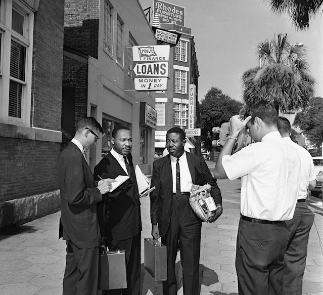 <p>Integration leader Martin Luther King, Jr., second from left, talks to a newsman on July 12, 1962, after he and Rev. Ralph Abernathy, second from right, walked out of jail after their fines were paid. Both said they did not know who paid the $178 fines. Far right is an unidentified city detective. Police arrested 32 African American demonstrators on July, 11, 1962 in Albany, Ga., when the group tried to march on City Hall. (AP Photo) </p>