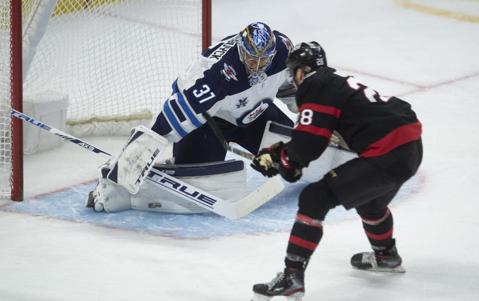 Winnipeg Jets goaltender Connor Hellebuyck, left, makes a save against Ottawa Senators right wing Connor Brown during second-period NHL hockey game action Monday, April 12, 2021, in Ottawa, Ontario. (Adrian Wyld/The Canadian Press via AP)