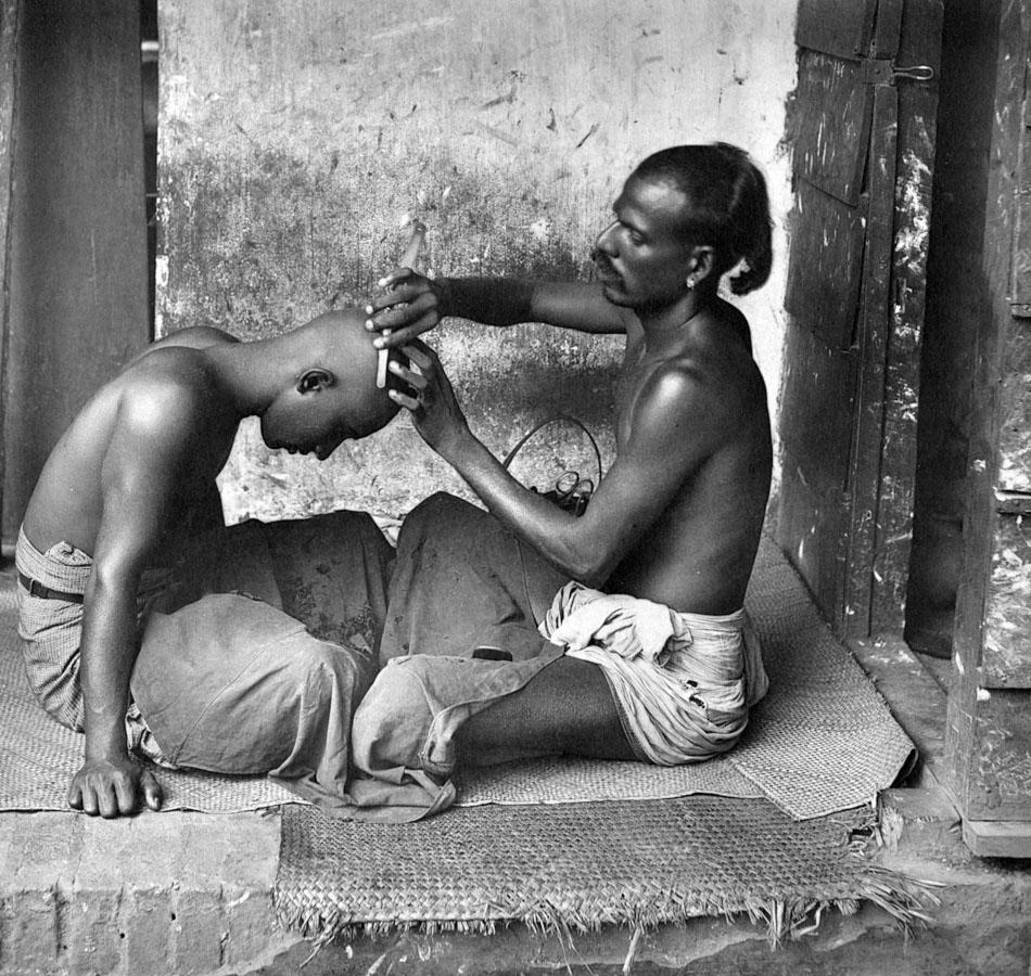 circa 1950: An Asian gives a friend a haircut, carefully shaving his scalp. (Photo by Hulton Archive/Getty Images)