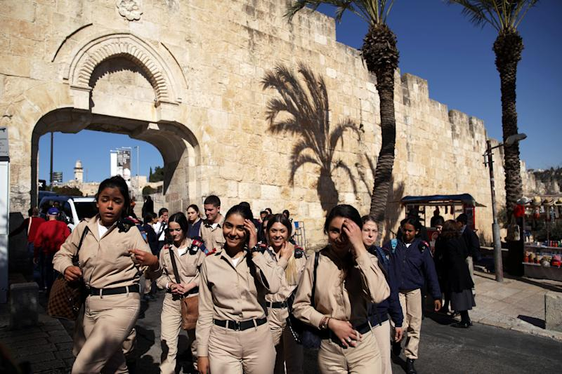 A group of female Israeli soldiers smile as they walk near Dung Gate in Jerusalem's Old City. (Photo: Nir Elias/Reuters)