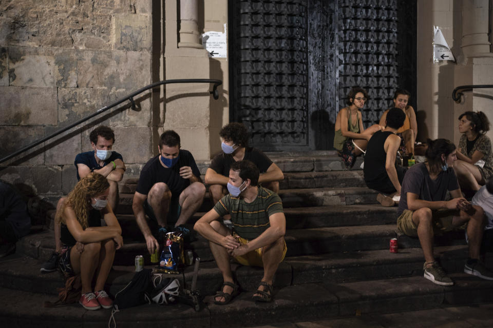 People gather at a public square at night in Gracia neighborhood, Barcelona, Spain, Friday, July 24, 2020. Health authorities in the northeastern region of Catalonia have ordered nightclubs to be fully closed and bars and restaurant in Barcelona to shut down by midnight in an effort to stem the spread of the new coronavirus. (AP Photo/Felipe Dana)