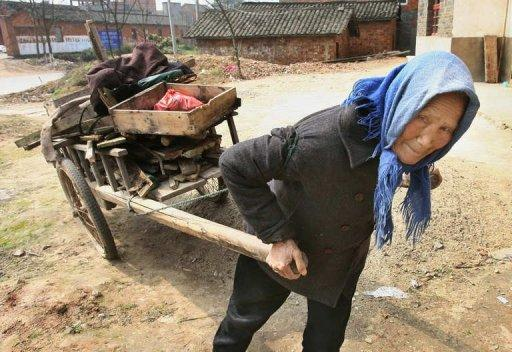An elderly Chinese woman uses a cart to collect firewood for cooking near the Yangtze river city of Jiujiang